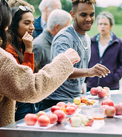 A diverse group of visitors tasting apples and cider at the Cornell Orchards