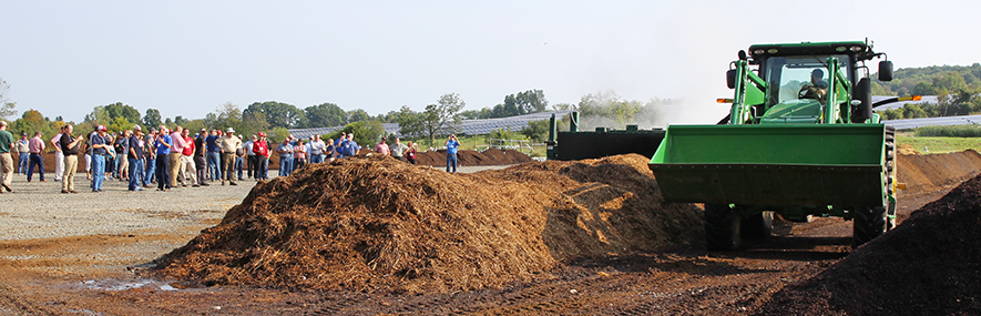 A group of managers from other research facilities watches a demonstration at Cornell's Compost Facility