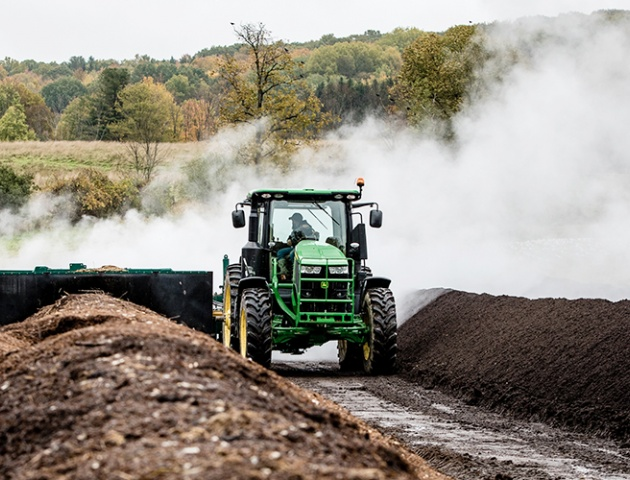 The windrow turner is turning compost at Cornell's compost facility