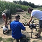 Researchers are preparing the rover and drone next to the corn field